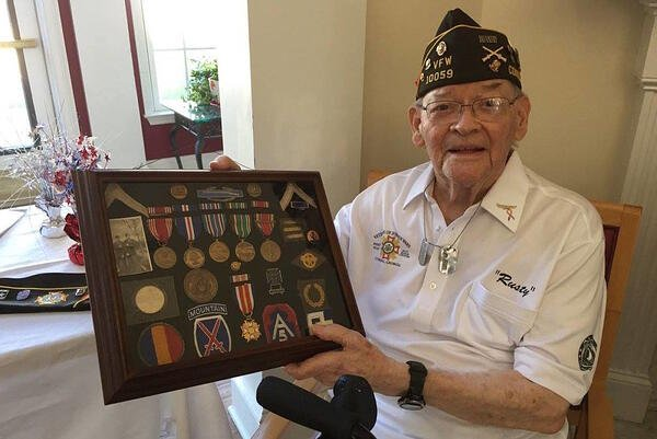 Image of elderly veteran holding medals