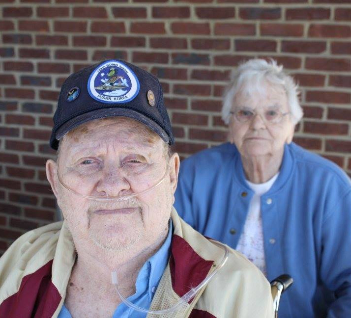 Image of elderly man wearing Veteran cap with woman behind him