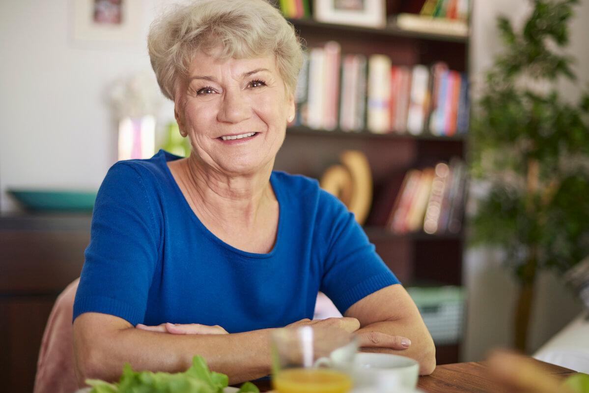 smiling-senior-woman-sitting-at- (1)